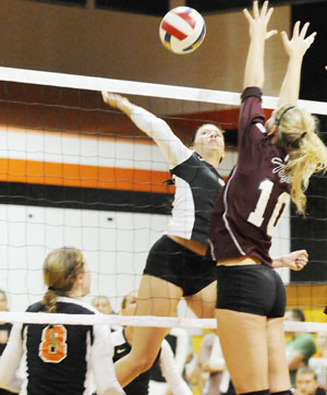 Kyla Welch (4) hits the ball in a match earlier this year off a set by Liz Goodin (8). Photo by Richard Davis.
