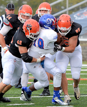 Brock Messina (42) sacks the Rams' quarterback with Michael Sherrard (85). Photo by Richard Davis.