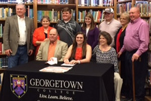 Beam on signing day with her family and GC coach Andrea McCloskey.