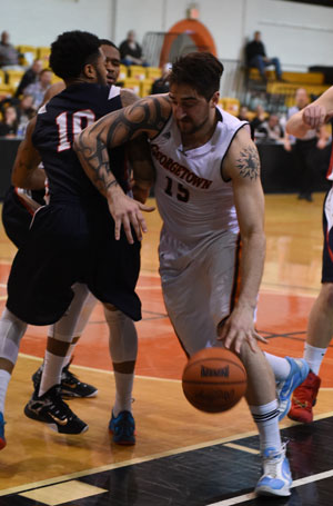 Levan Shengelia drives around a UC defender on Senior Day. Photo by Richard Davis