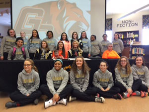Martina Lytle, center, signs with Georgetown surrounded by her Fleming County High School teammates.