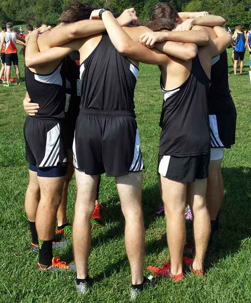 Men's cross country huddle up and pray before Saturday's race.